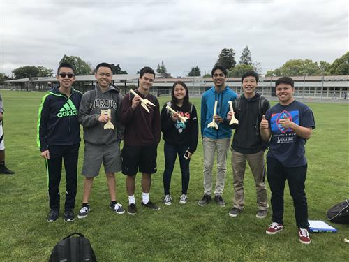 Physics students in a field testing rockets